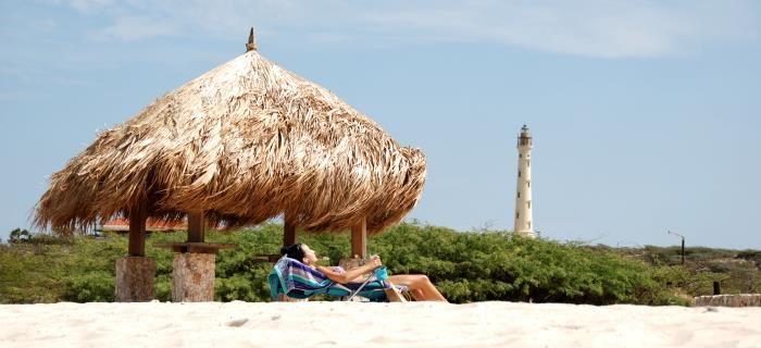 Arashi Beach - vrouw ligt op strand te zonnen met de vuurtoren op de achtergrond