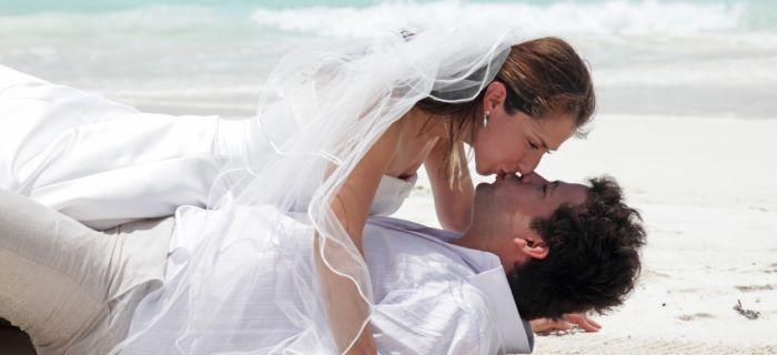 Een net getrouwd stel kussen elkaar op het strand