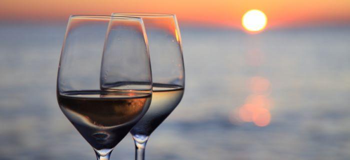 Een glas wijn drinken bij zonsondergang