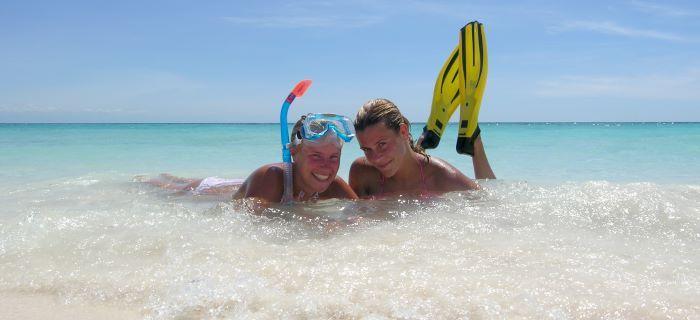 Meiden op het strand met hun snorkel, duikbril en flippers