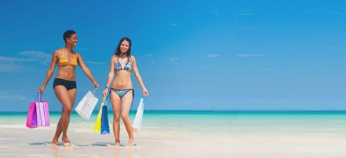 Meiden met winkeltassen op het strand