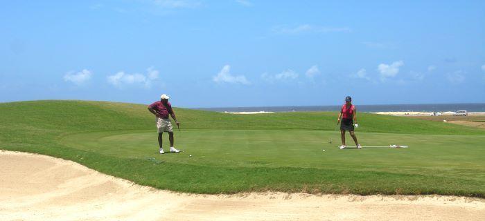Een stel speelt golf aan de noordkust van Aruba