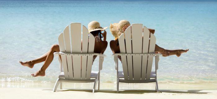 Vrouwen zitten op strandstoelen op het strand